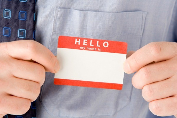 A man adhering a sticky name badge label to his dress shirt.