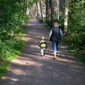 A mom and child walking in the woods.
