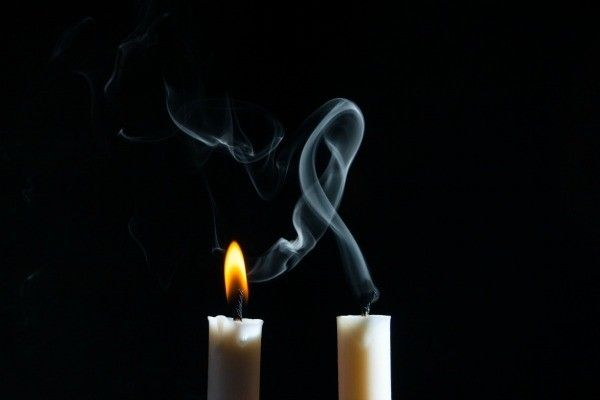 Two candles, one lit and one just put out with smoke above.