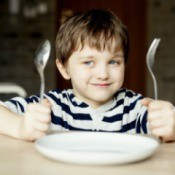 A boy waiting for dinner with an empty plate.