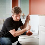 A man using a plunger in a toilet.