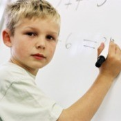 A boy writing on a white board with a dry erase marker.
