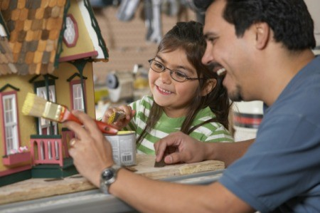 A father painting a dollhouse with his daughter.