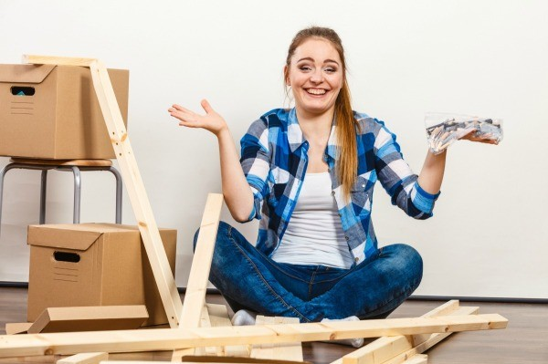 A woman putting together a piece of furniture with parts in her hands.