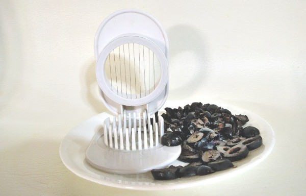 egg slicer on a plate with sliced olives