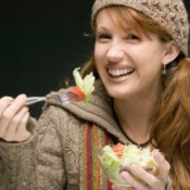 A woman eating a salad in a wool sweater.