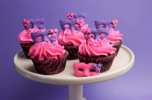 Cupcakes decorated with masquerade masks in purple and pink.