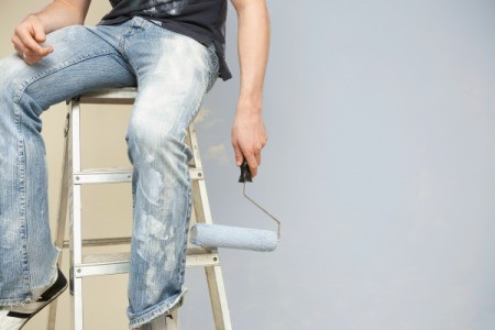 A man painting and wearing paint spattered jeans.