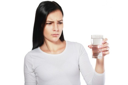 A woman looking concerned at a glass of water.