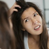 A woman noticing dandruff in her dark hair.
