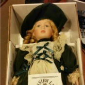 doll in dark dress with matching hat in box