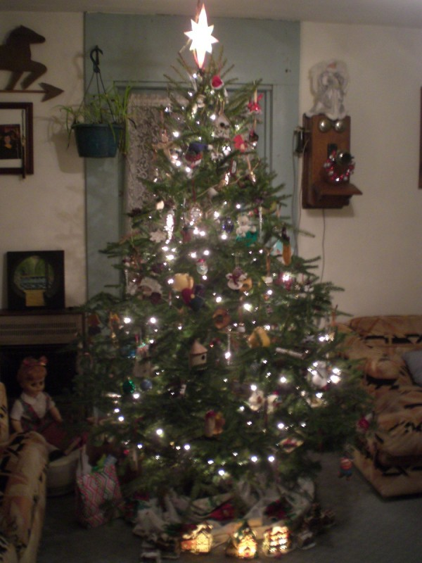 A decorated and lighted Christmas tree in a living room.