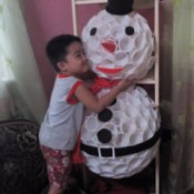 little boy hugging the snowman
