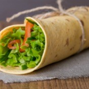 A tortilla sandwich wrap with lots of fresh veggies.