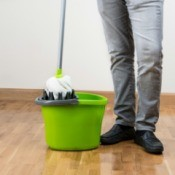 A mop and bucket on a hardwood floor.