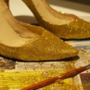 A pair of shoes that have been painted with gold glitter.
