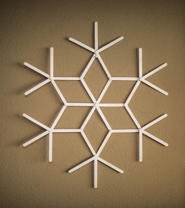 A finished popsicle stick snowflake, painted white.