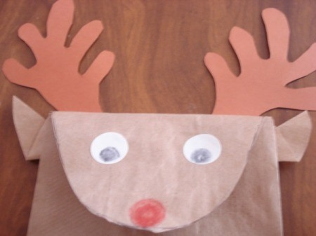 Closeup of finished reindeer paper bag face with the addition of nose and eyes.