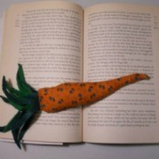 A book weight shaped like a carrot, holding open a book.