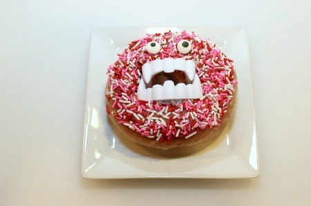 A sprinkled donut with vampire fangs.