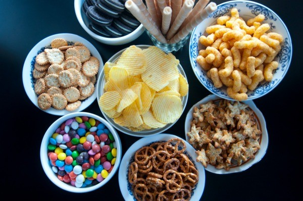 A bunch of bowls of salty snack foods.