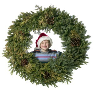 A boy smiling looking through the opening of a giant Christmas wreath.