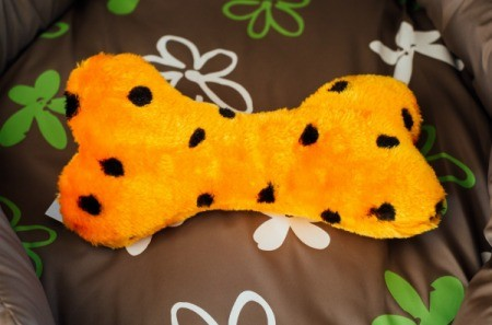 An orange and black bone shaped dog toy with a squeaker inside.