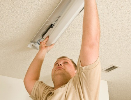 A man fixing a fluorescent light.