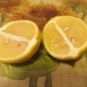 A yellow lemon cut in half, ready for use.