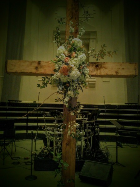 A cross adorned with flowers for a wedding.
