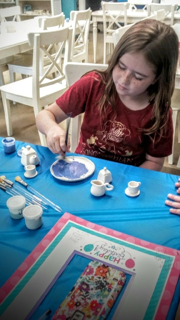 A girl painting a piece of pottery at a birthday event.