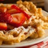 Homemade funnel cakes with powdered sugar and strawberries on top.
