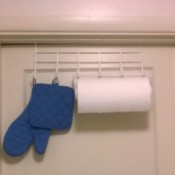 An over the door hook with paper towels and hotpads.