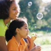Mother and daughter blowing bubbles.