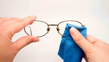 Cleaning glasses with a  microfiber cloth and cleaner.