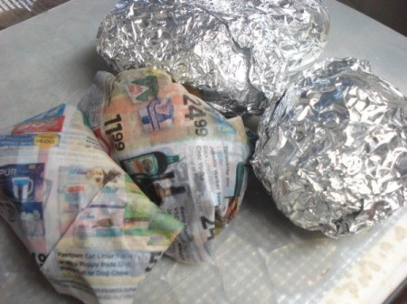 potatoes wrapped in foil and eggs wrapped in newspaper