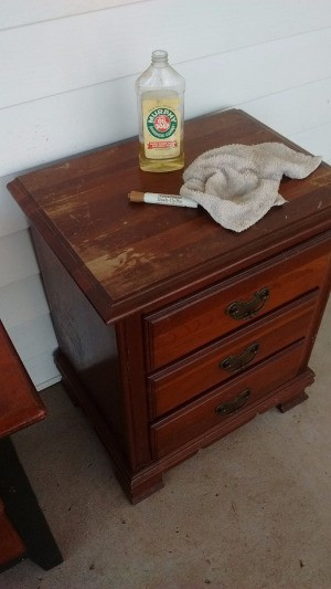 How to Fix Damaged Surfaces of Wood Furniture - small chest of drawers with bottle of oil soap, furniture pen, and rag on top