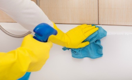 person wearing rubber gloves cleaning a bathtub