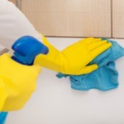 Person wearing rubber gloves cleaning a bathtub.