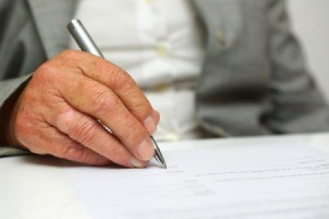 Older man signing a legal document.