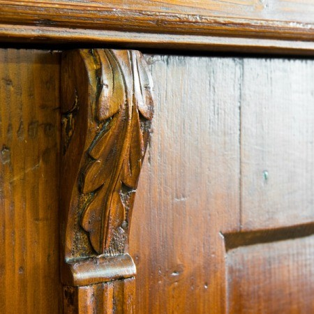 Close up leaf pattern detail of a piece of antique wooden furniture.
