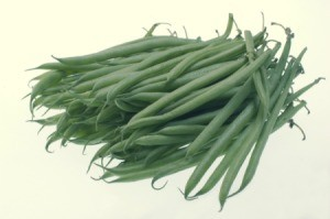 A pile of green beans on a light background.