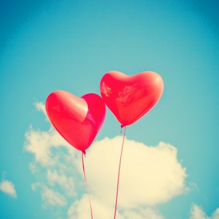Two heart shaped red balloons in a blue sky with clouds.