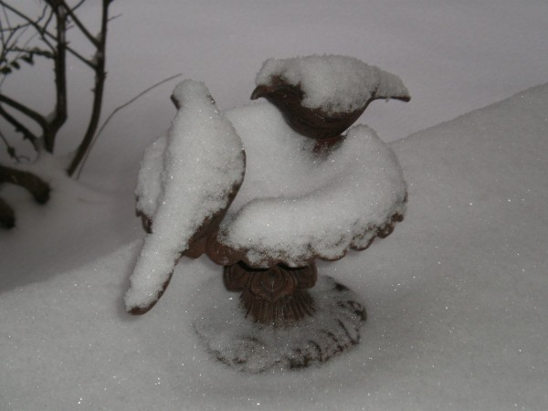 A birdbath with concrete birds covered in snow.