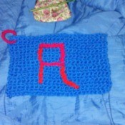"A crocheted dishrag with a letter ""A""."