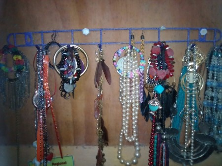 A mug rack with jewelry displayed on it.