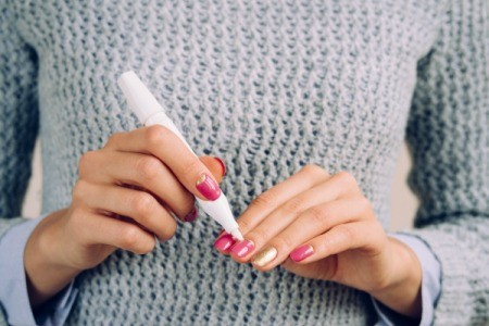 A woman in a grey sweater doing a manicure on herself.