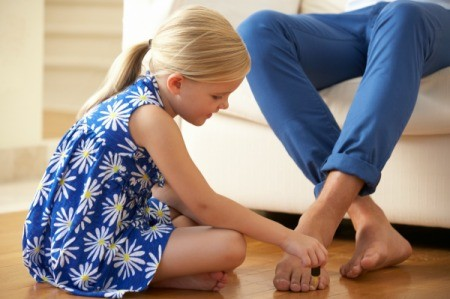 A young girl painting her father's toenails.