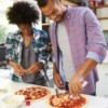Couple making pizza together at home.