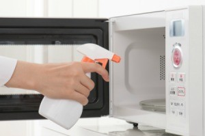 Cleaning solution being sprayed into a microwave.